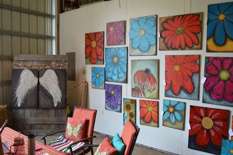 Wall of flower paintings on display during the Rural Arts Roadtrip