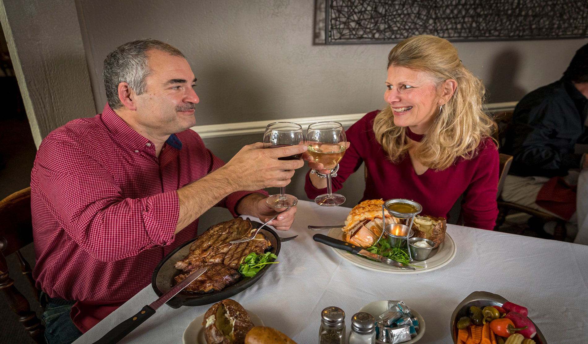 Man and woman cheersing while eating dinner.