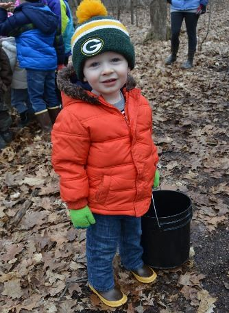 Little boy in orange coat holds a bucket for sap at Maple Syrup Sunday