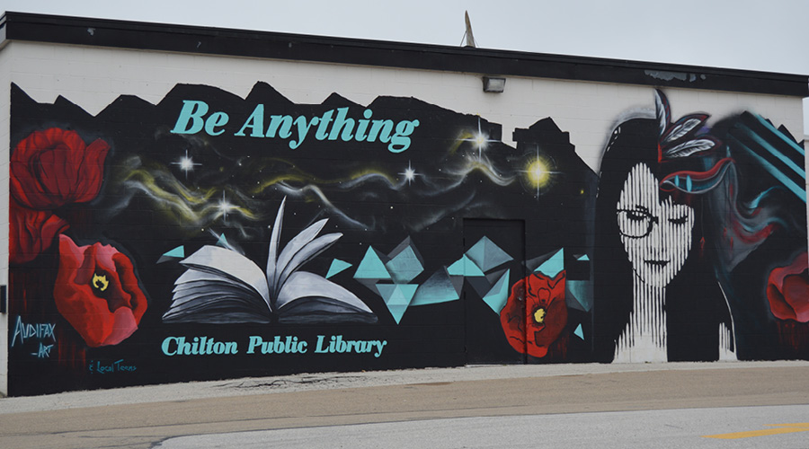Chilton Library Mural with the image of a woman, book, and flowers.