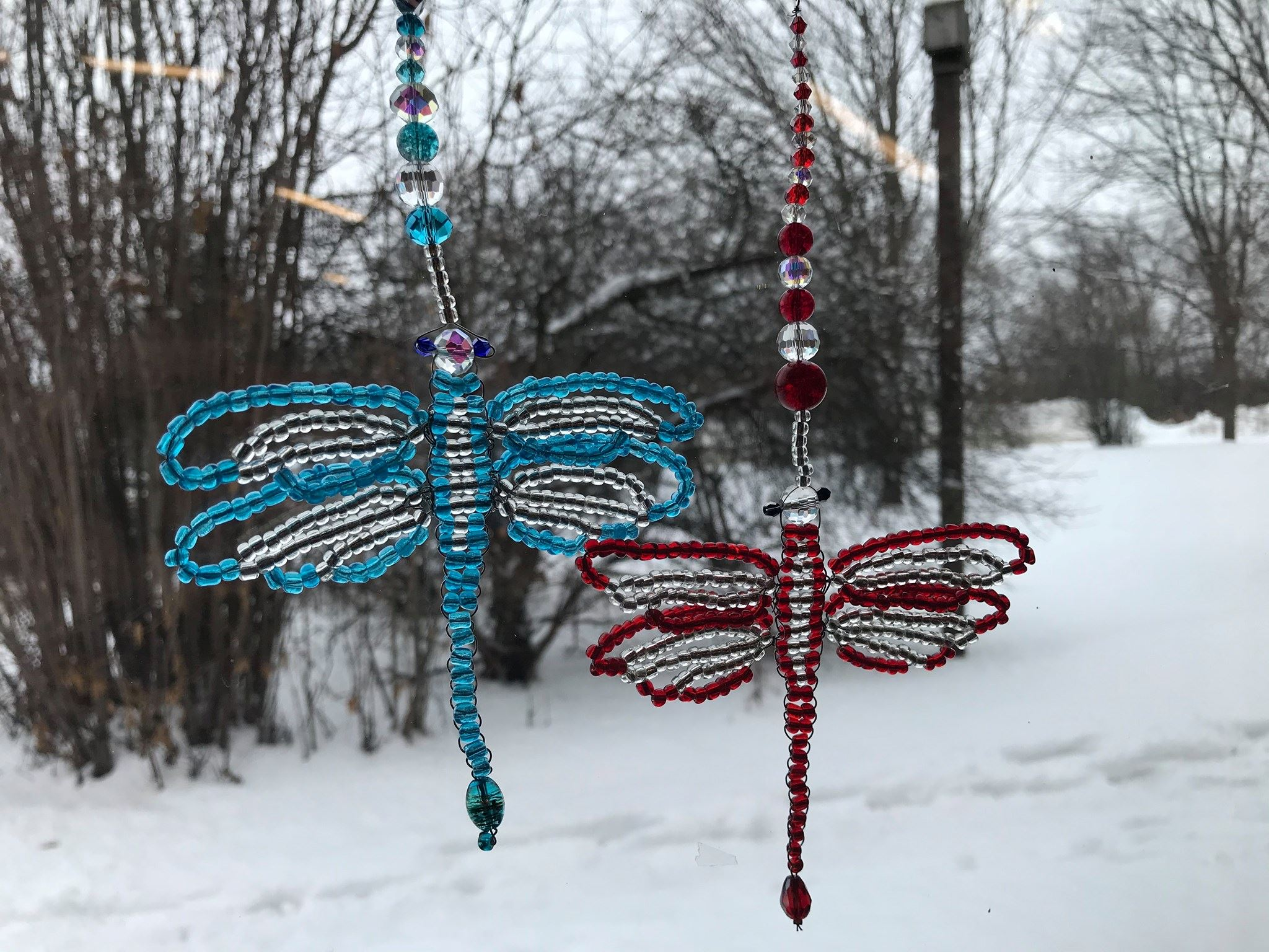 dragonfly suncatchers made up of gem beads displayed in front of window with snow in the background.