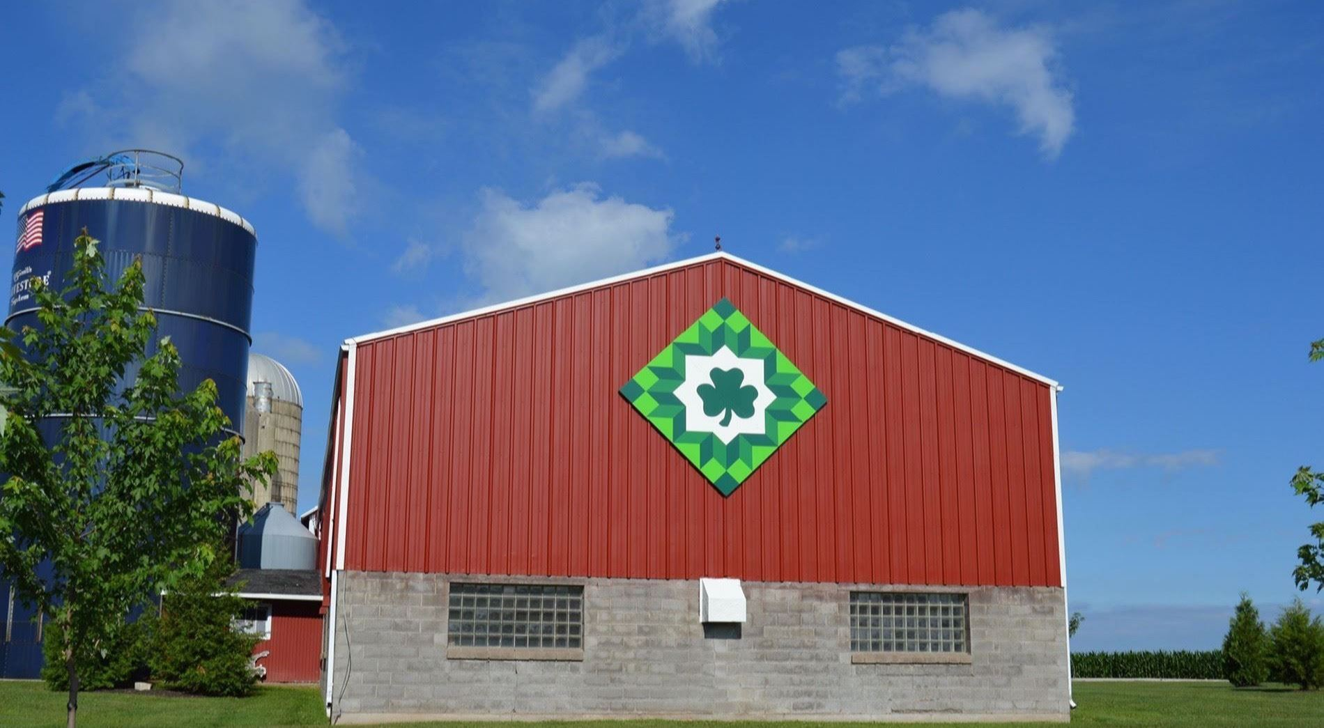 Image of barn quilt on the side of a red barn.