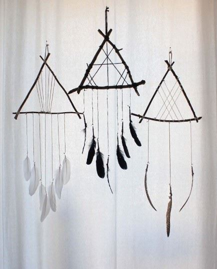 A hanging mobile dreamcatcher made from sticks and feathers and string.