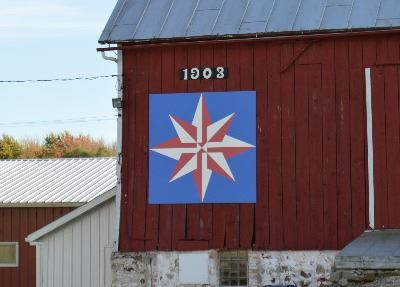 Red and white compass star on a barn quilt with a blue background on a red barn.