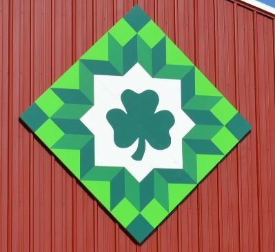Barn quilt in a diamond pattern on the side of a red barn. Barn quilt is different shades of green w