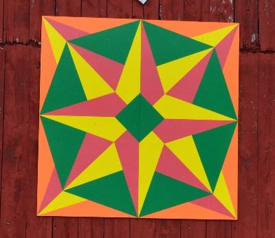 Barn quilt on a red barn. Barn quilt depicts compass star with orange and green border with yellow a