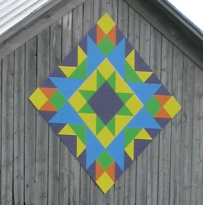 Barn quilt in a diamond pattern on the side of an unpainted barn. Pattern is a multicolored star bur