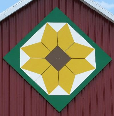 Brown-Eyed Susan on a barn quilt in a diamond pattern on a red barn. The Brown-Eyed Susan is surroun