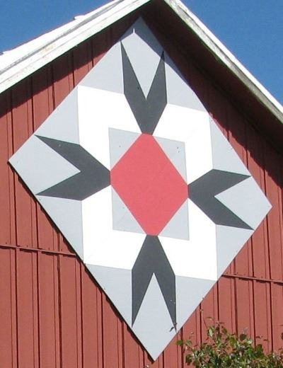 Barn quilt in a diamond pattern on the side of a red barn. Barn quilt has a red diamond in the cente