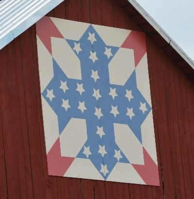 Barn quilt on the side of a red barn. The pattern is in the shape of a cross that is blue with white