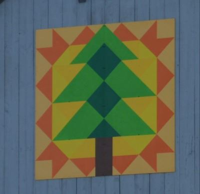 Barn quilt on the side of a white barn. Pattern includes a large pine tree with the sun in the backg