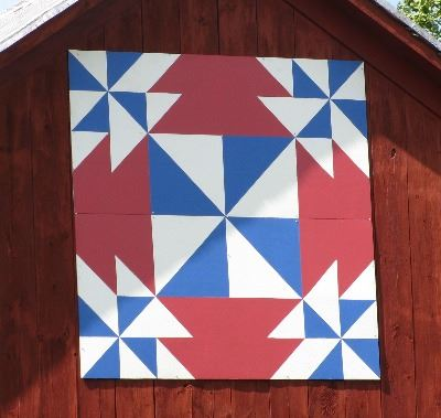 Barn quilt on the side of a red barn. Pattern is blue and white triangles with a red background.
