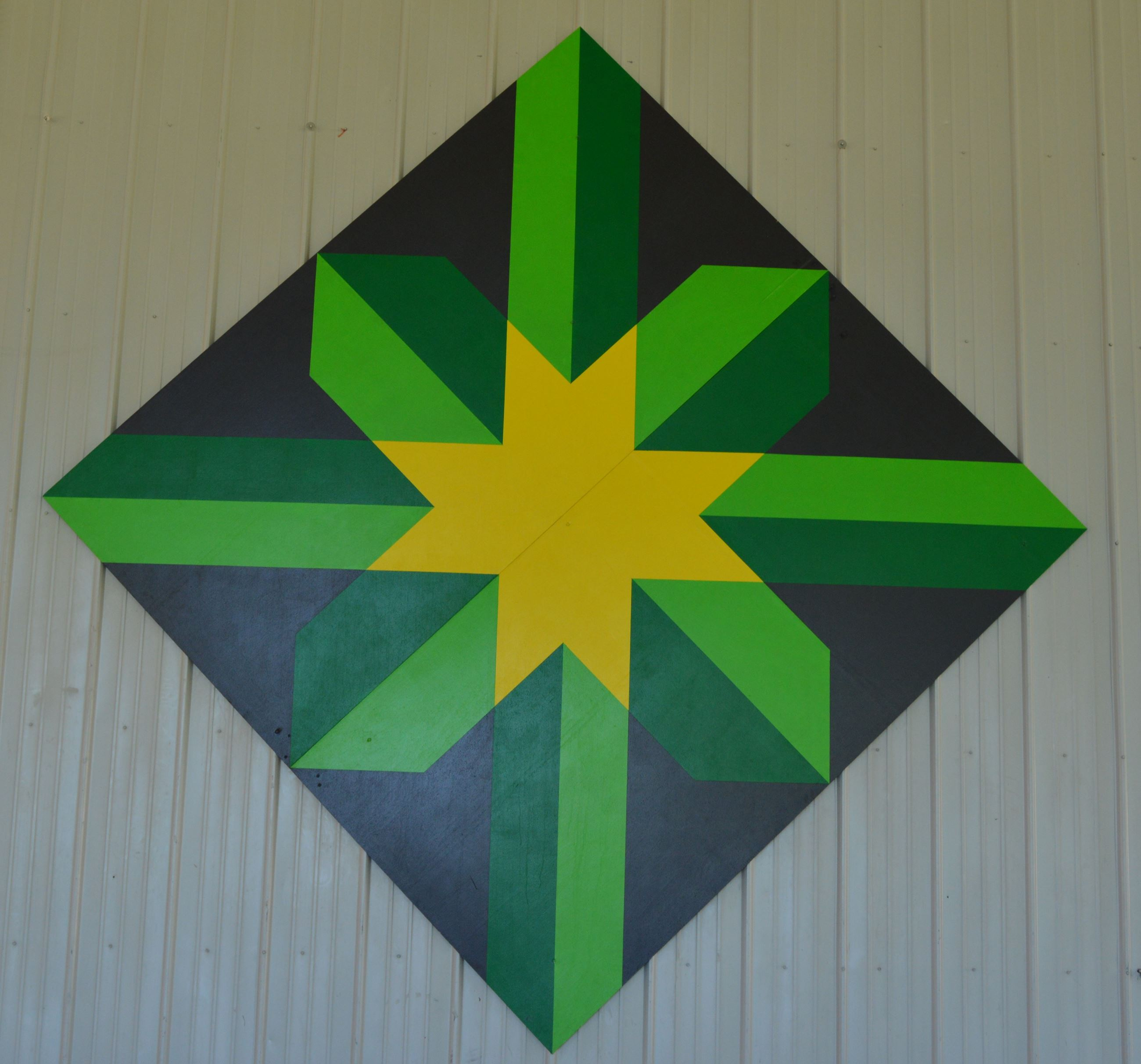 Barn quilt in a diamond shape on the side of a white steel wall. Pattern includes green intersecting
