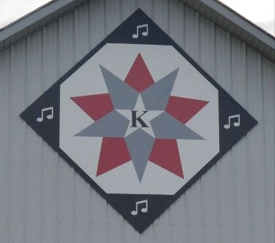 Barn quilt in a diamond shape on the side of a red and white barn. Barn quilt pattern includes a gra