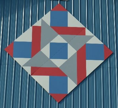 Barn quilt in a diamond shape on the side of a blue barn. Barn quilt pattern includes squares, trian