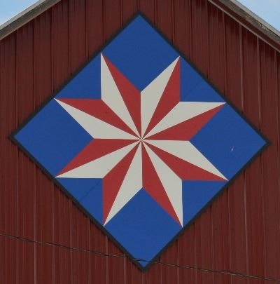Barn quilt in the shape of a diamond on the side of a red barn. Barn quilt pattern in the shape of a
