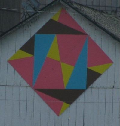 Barn quilt in diamond shape on the side of a white barn. Pattern includes multiple triangles in blac