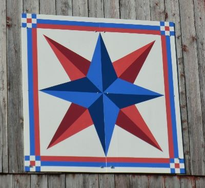 Barn quilt on the side of a weather-worn barn. Pattern is of a compass star painted red and blue wit