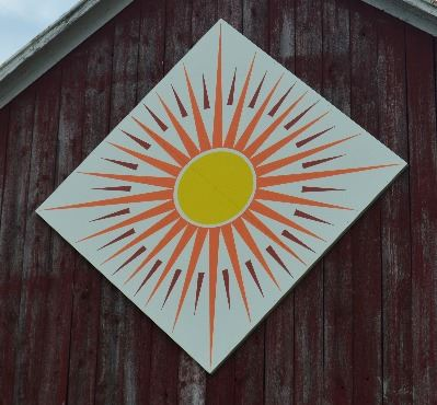 Barn quilt in a diamond shape on the side of a red barn. Pattern is of a sun in the center with red