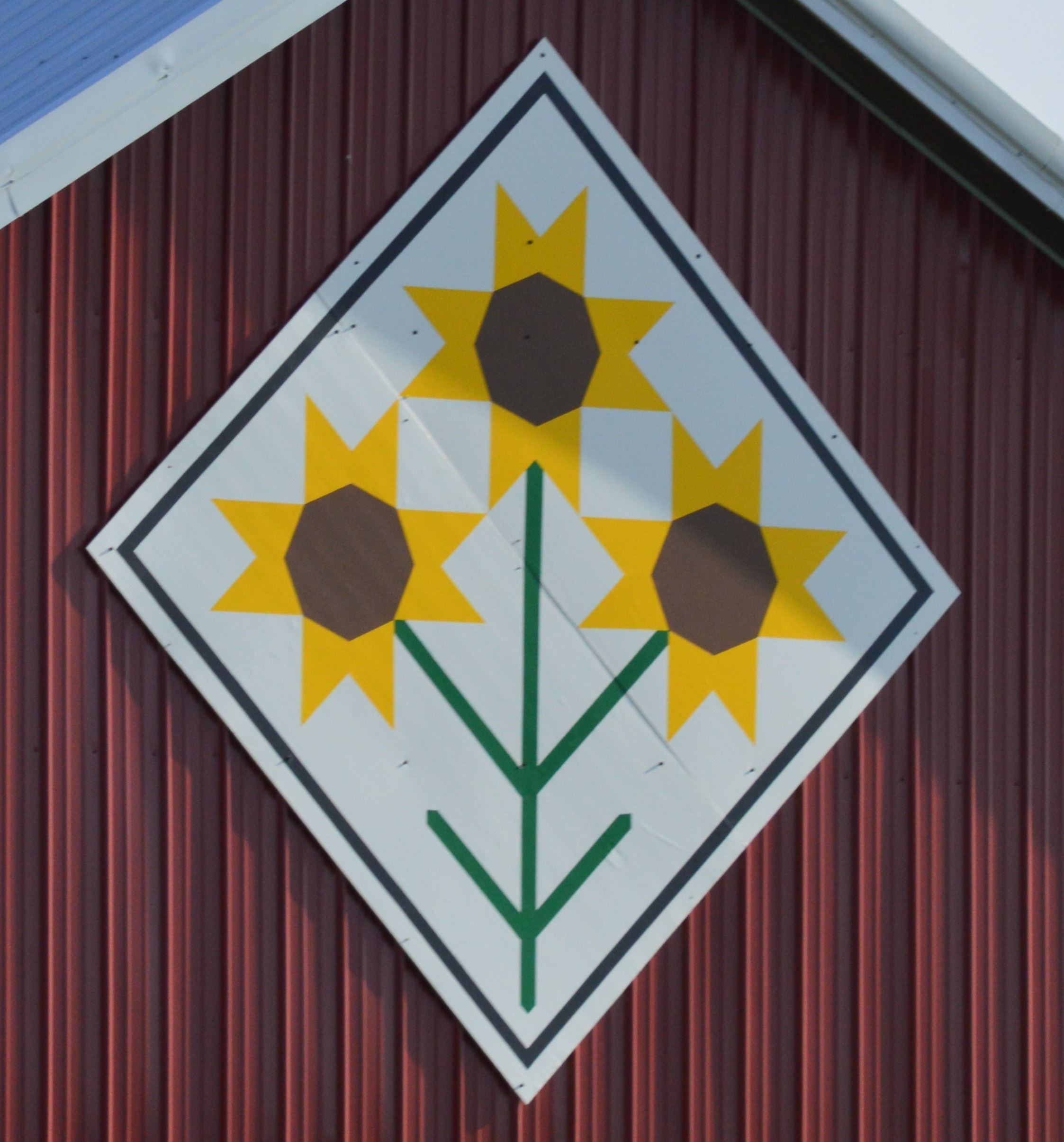 Barn quilt in a diamond shape on the side of a red barn. Pattern is of three sunflowers with a white