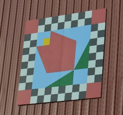 Barn quilt on the side of a red barn. The pattern is of a red tulip in the center with a blue backgr