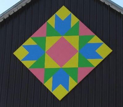 Barn quilt in a diamond pattern on the side of a brown and white barn. Pattern is of various triangl