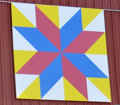 Barn quilt on the side of a red barn. Pattern is of a red and blue star burst with a white and yello