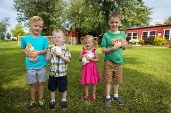 Four kids each holding a bunny at Mulberry Lane Farm